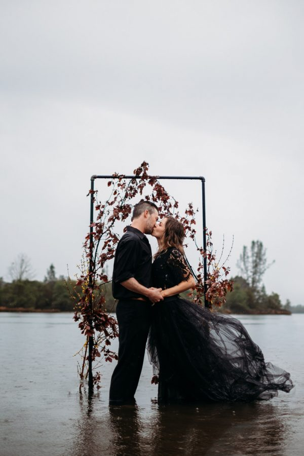 beautiful elopement in the waters on a raining day in all black attire