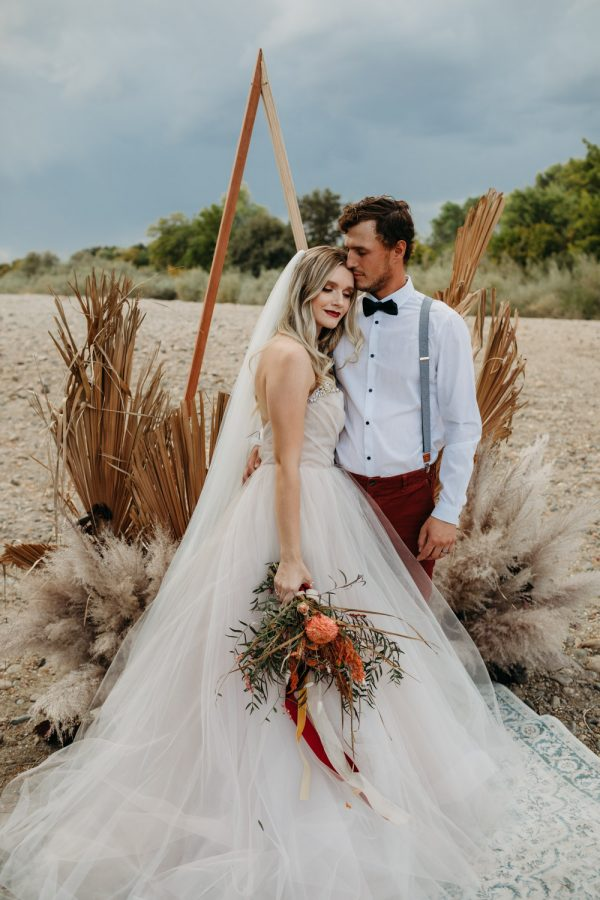 hipster boho couple elopement with blush wedding dress and cool black hat. Triangle wooden arch for the ceremony and dry pampasopement with blush wedding dress and cool black hat
