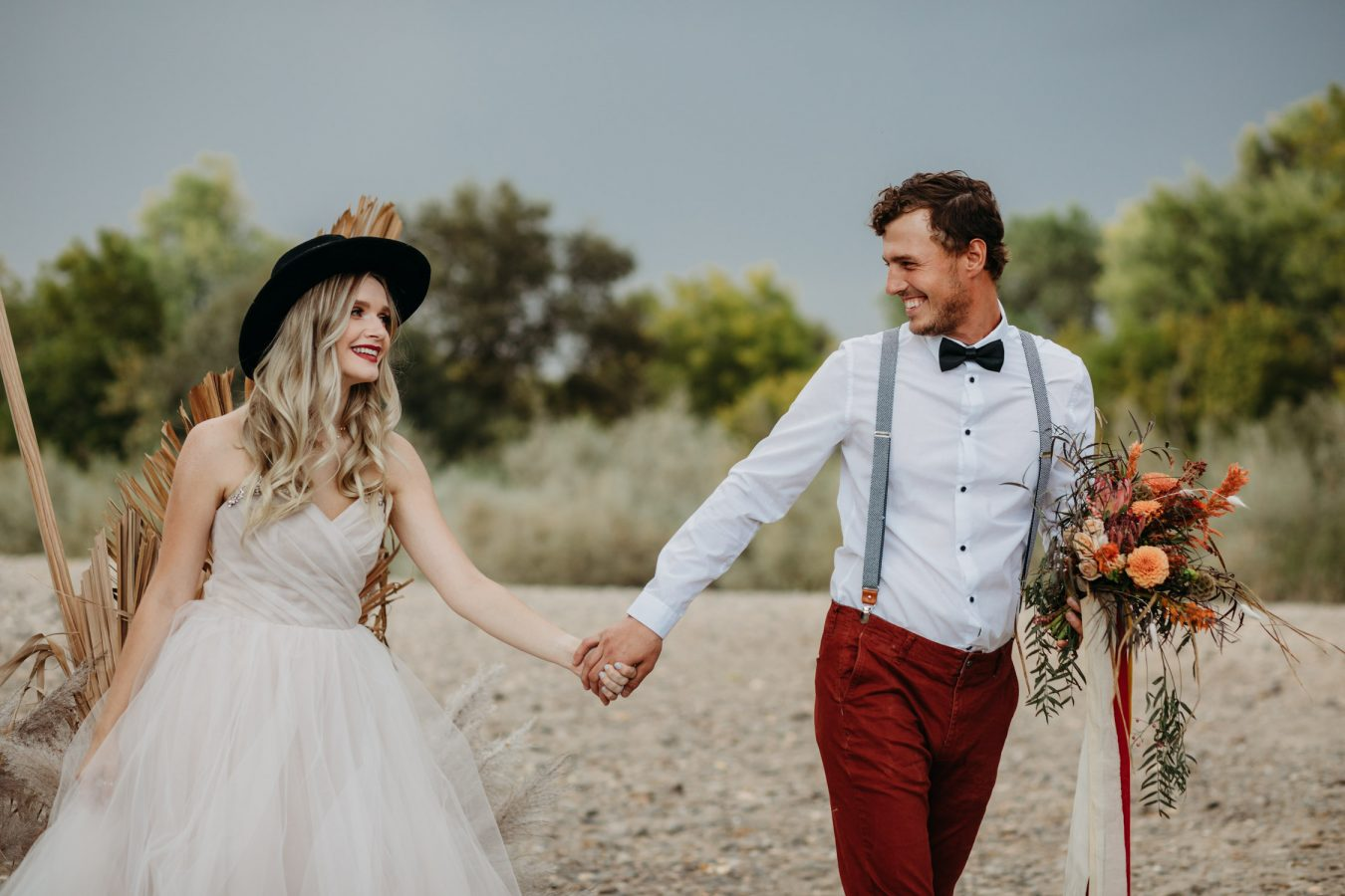 hipster boho couple elopement with blush wedding dress and cool black hat